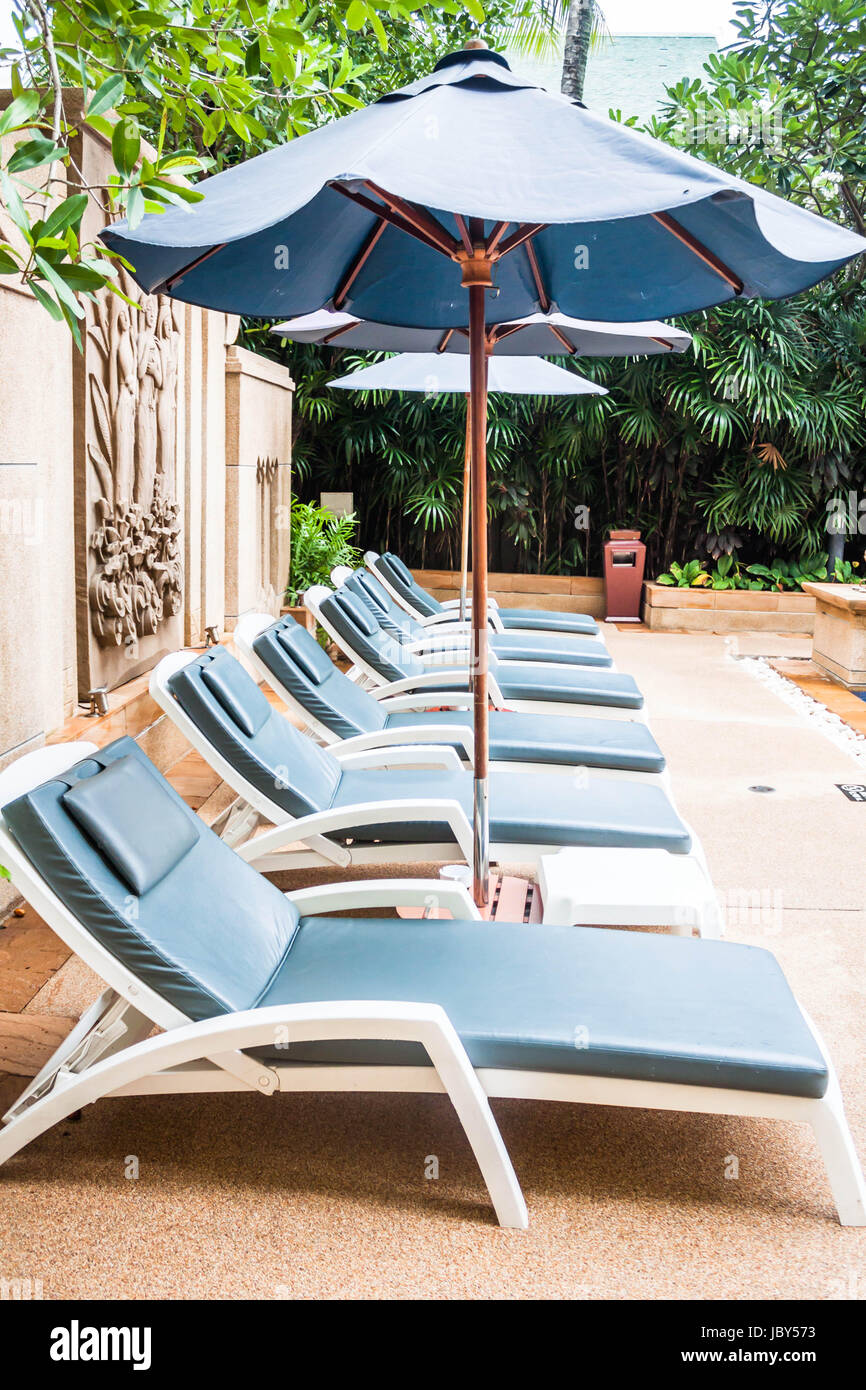 Beach chairs and umbrellas beside hotel swimming pool Stock ...