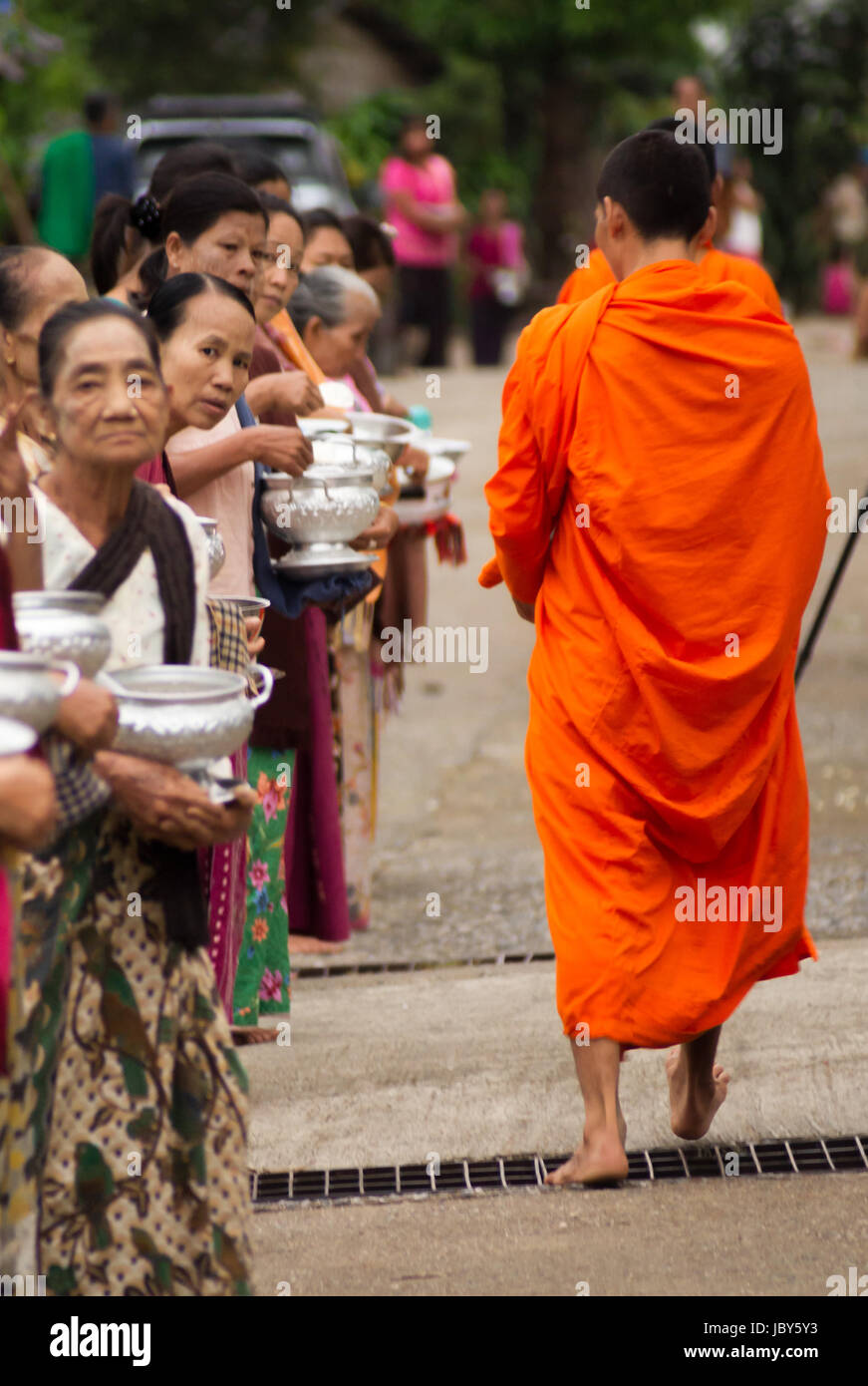 THAILAND, SANGKHLA BURI - NOVEMBER 21, 2012: Buddhist monks collecting alms and food given by the local people in Stock Photo