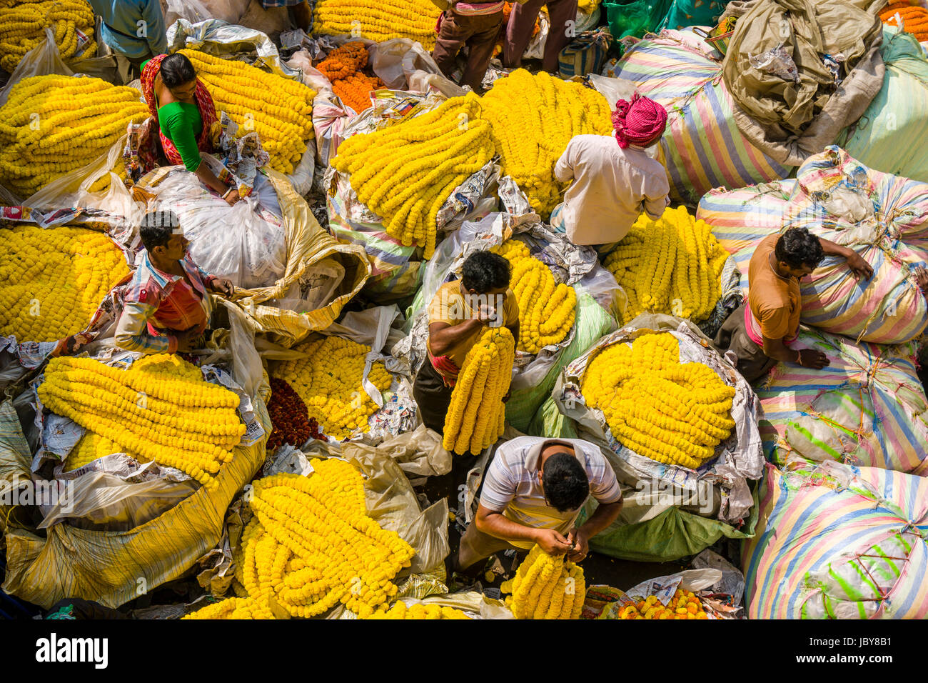 Heaps of colorful marygold flowers are sold by vendors on the daily flowermarket below Howrah Bridge - Stock Image