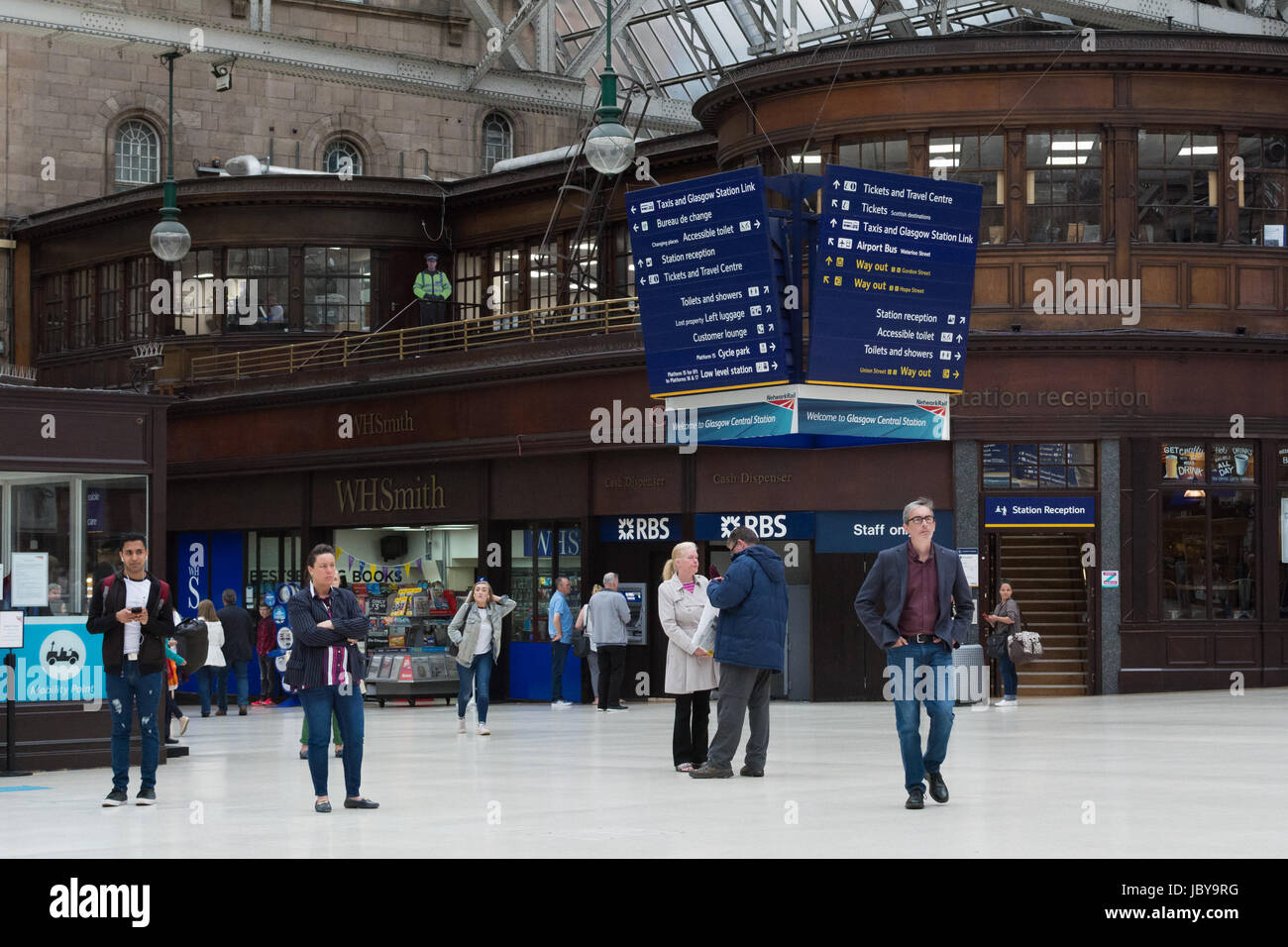 Glasgow Central Station with a cardboard cutout police officer top left - Stock Image