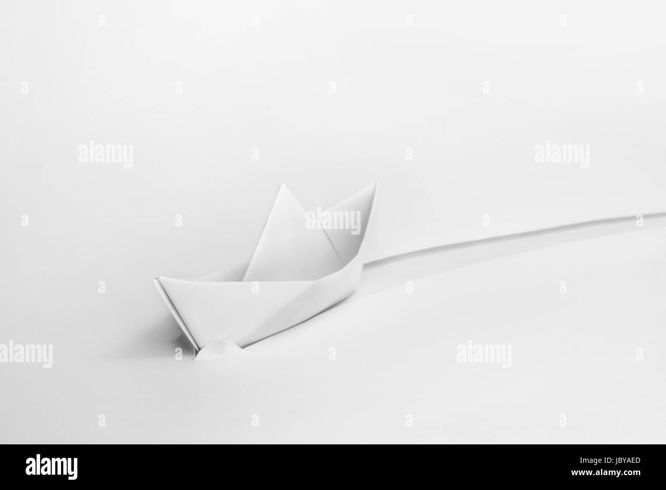White paper origami boat cuts through paper. - Stock Image