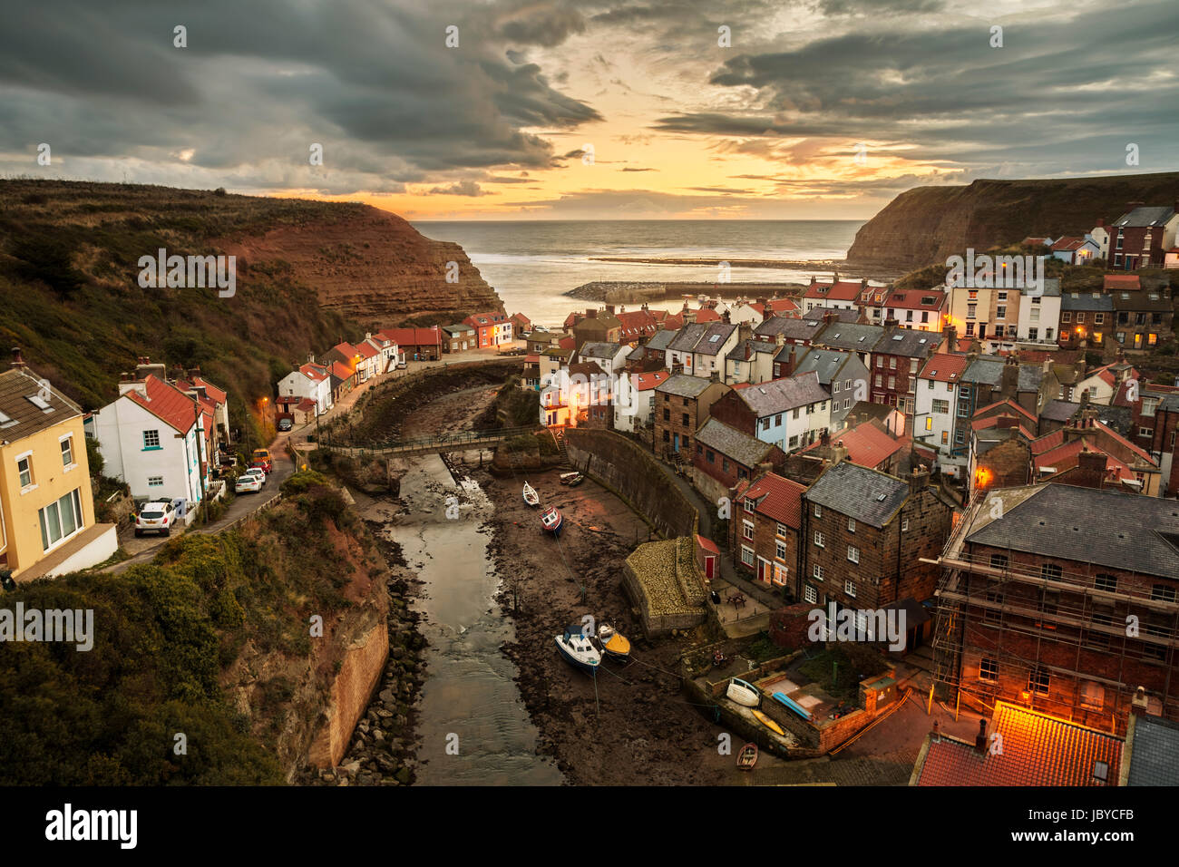 Dawn as the sun begins to rise over the beautiful fishing village of Staithes, nestled into the cliffs of the North - Stock Image