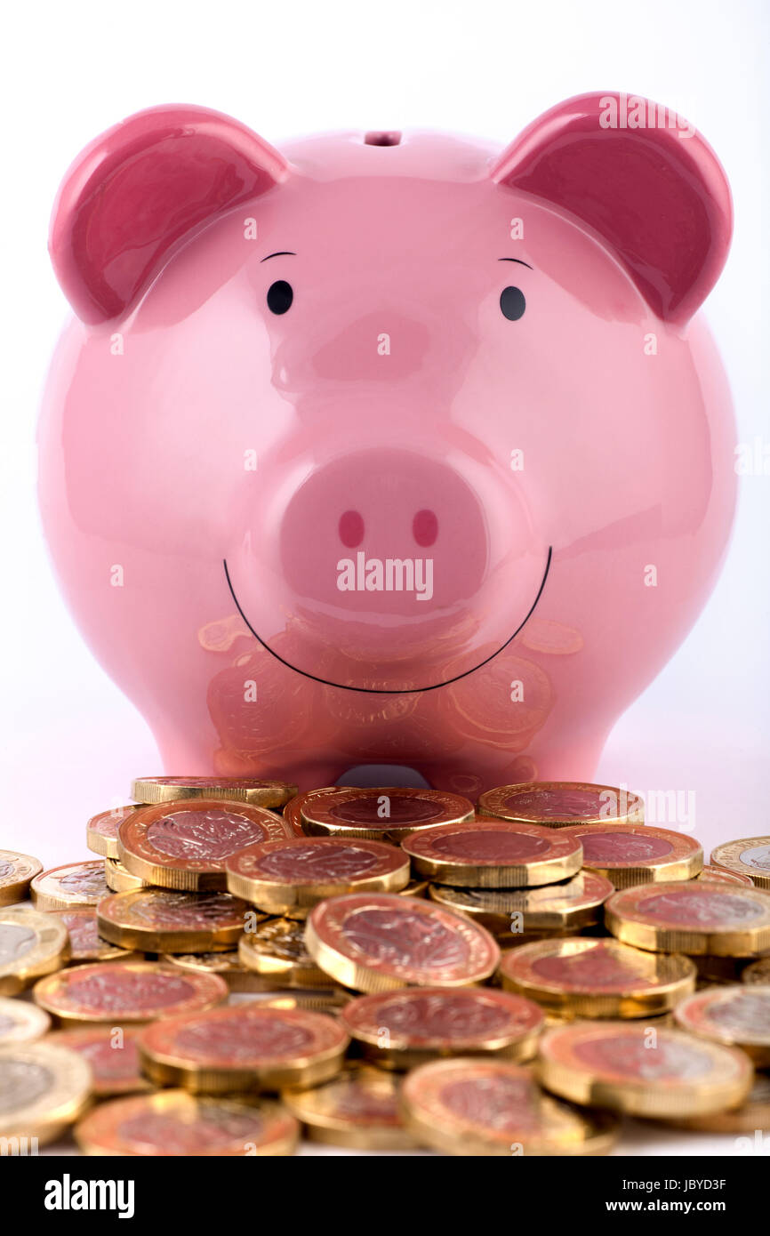 Piggy bank with a pile of new 2016/2017 one pound coins. - Stock Image