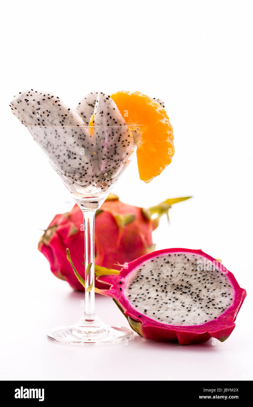 Wedges of a pitaya assorted in a glass and decorated with a mandarine slice. Next to it a halved, and behind it, - Stock Image