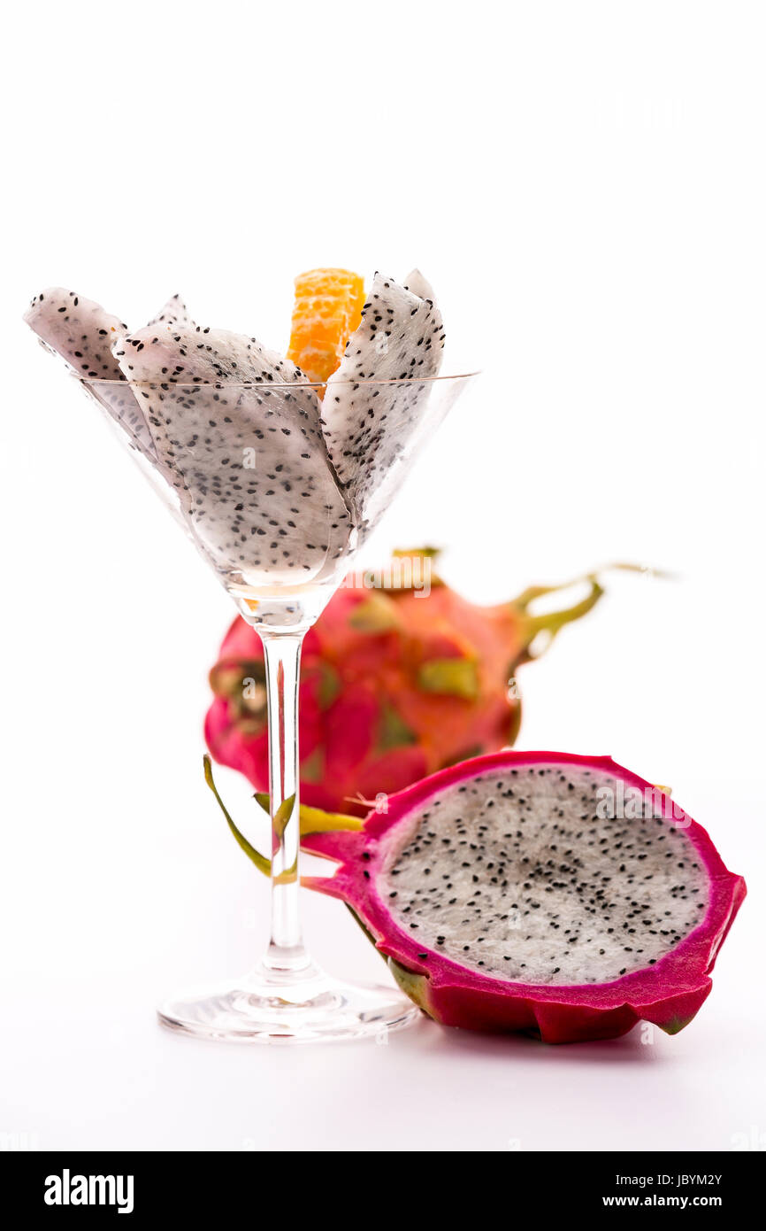 White fruit wedges of a pitaya assorted in a glass and adorned with a mandarine slice. Next to it, the fruit pulp - Stock Image