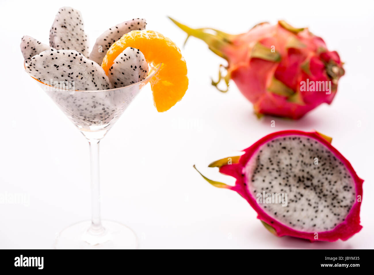 The juicy pulp of the Pitahaya blanca presented in a glass and decorated with a mandarine slice. This exotic fruit - Stock Image