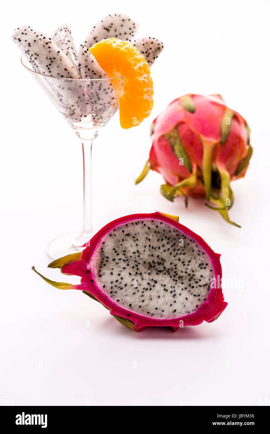 A longitudinal section of a pitaya. Its white pulp is covered with a vibrant violet skin. Its flavor is in harmony - Stock Image