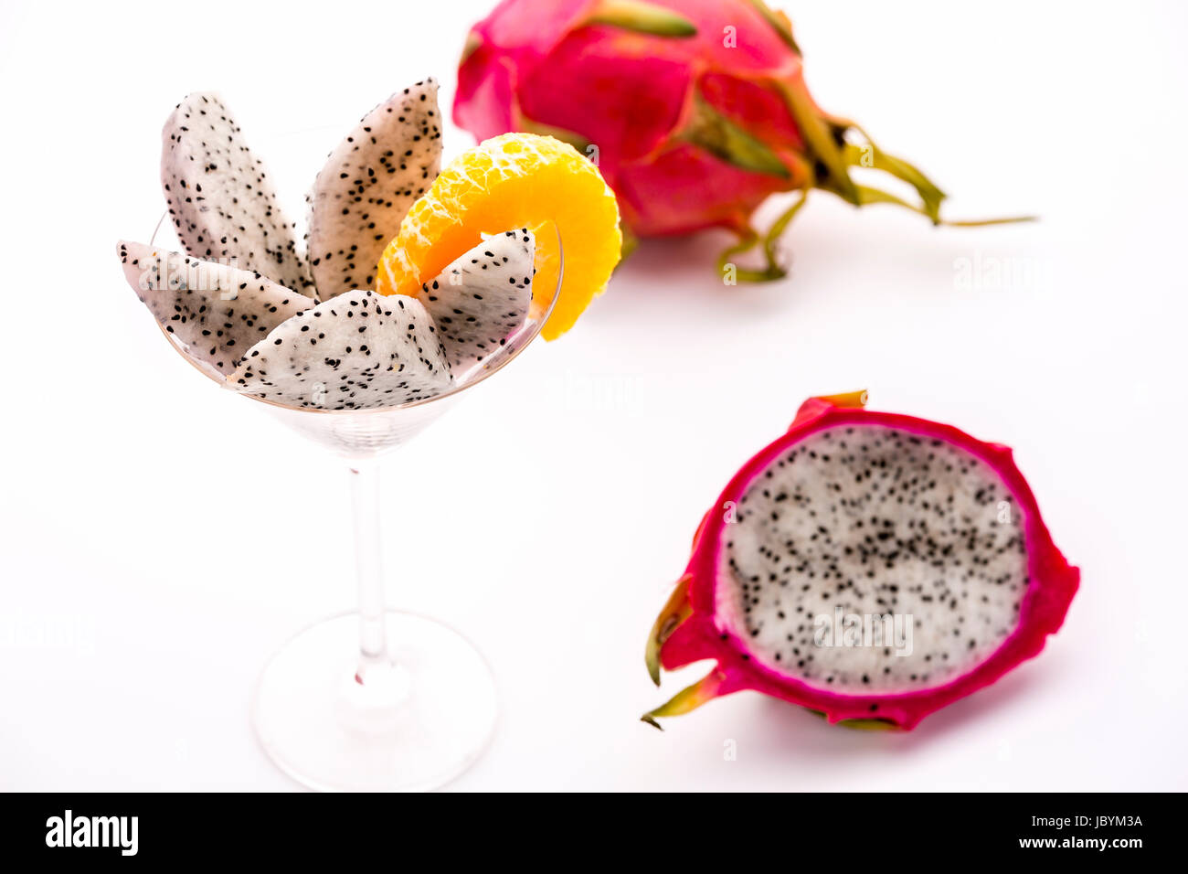 White pulp of half a pitaya cut into wedges and presented in a glass. The decorative mandarine slice is also complementing - Stock Image