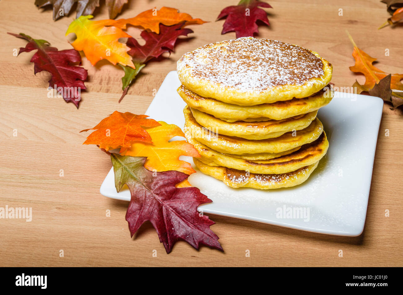 Fresh pancakes topped with powdered sugar with fall leaves - Stock Image