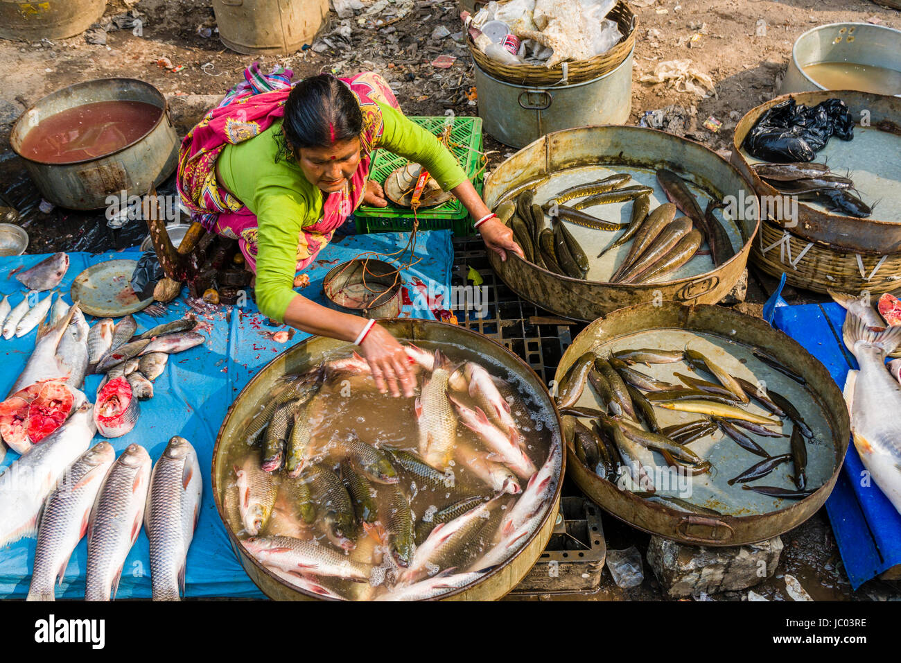 A woman is selling fish on a busy vegetable market street in the suburb New Market - Stock Image