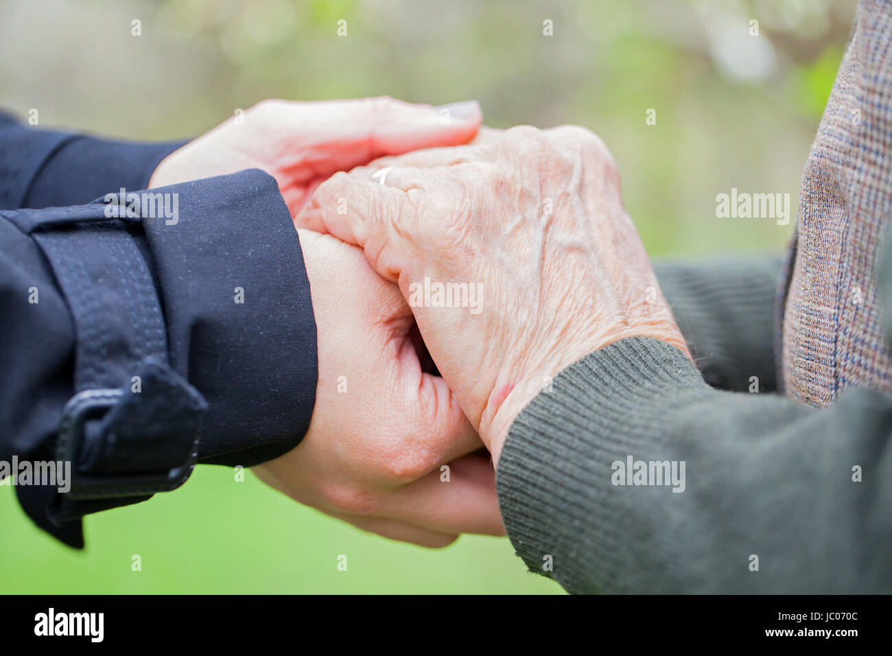 Close up picture of a young woman's hands holding an elderly female's hands Stock Photo