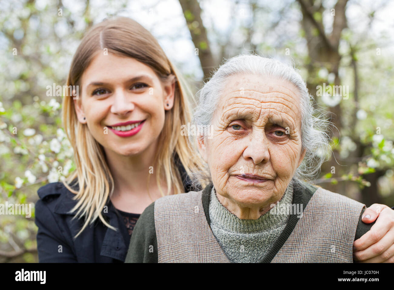 Portrait of a sick elderly woman with her young carer in the park - Stock Image
