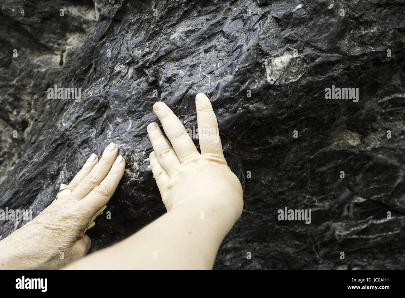 Hands in cave of religious lourdes, faith and catholic belief - Stock Image