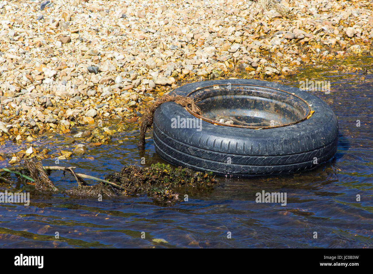 A disused tyre and rim polluting a small stream on the Solent Way beach on Southampton Water near Titchfield in - Stock Image