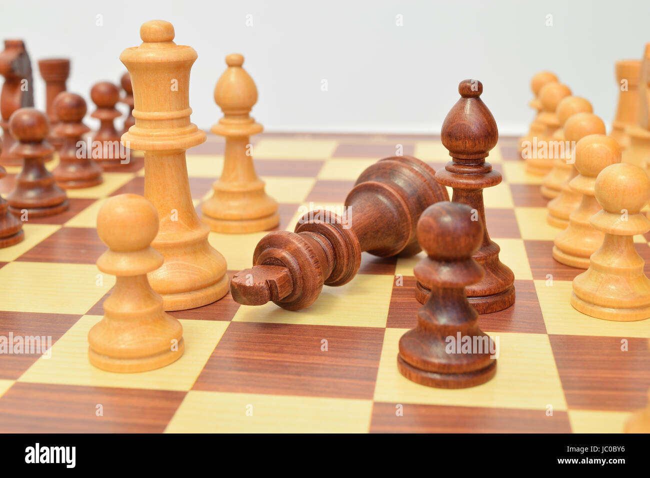 King at the foot of various pieces on the chessboard Stock Photo