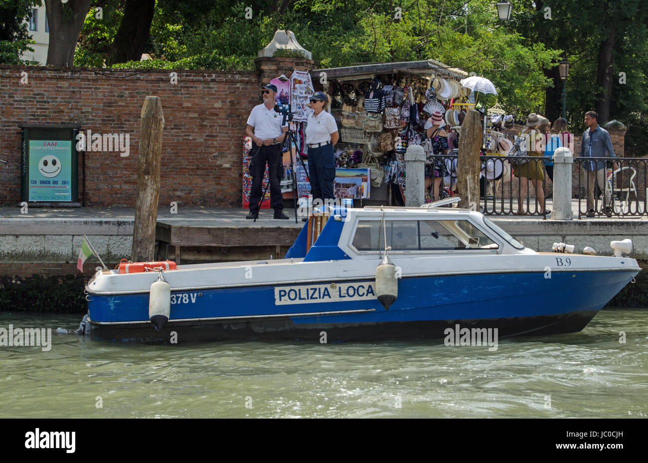 VENICE, ITALY - JUNE 13, 2017:  Two police officers operating a speed trap beside a busy stall selling tourist souvenirs Stock Photo