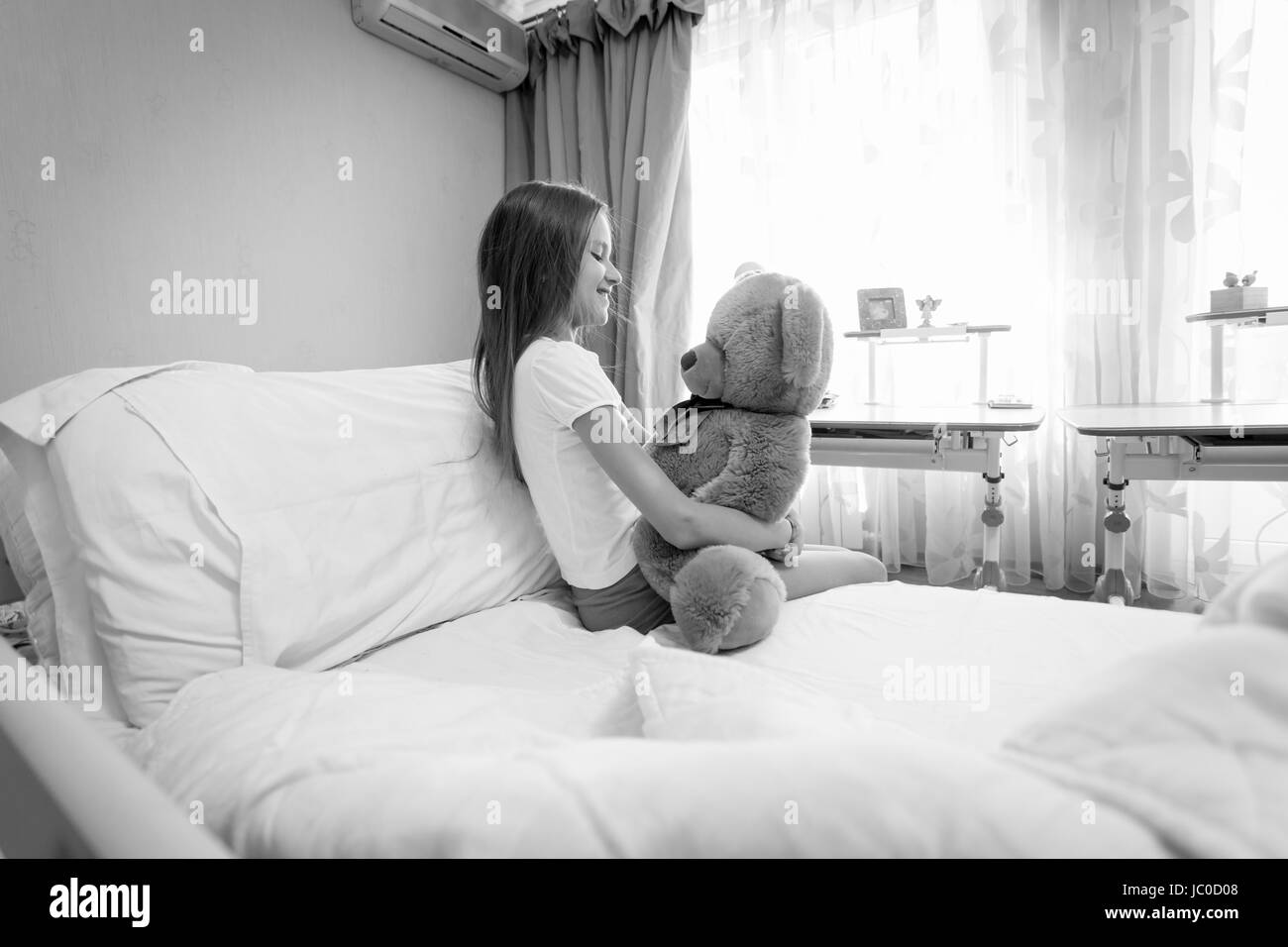 Black and white portrait of cute girl sitting on bed and hugging her teddy bear - Stock Image