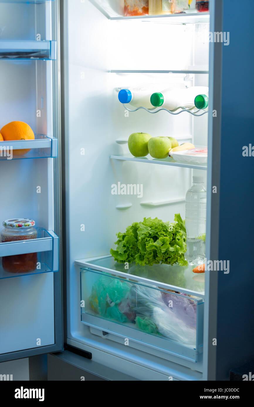 Open refrigerator full of food on kitchen at night Stock Photo ...