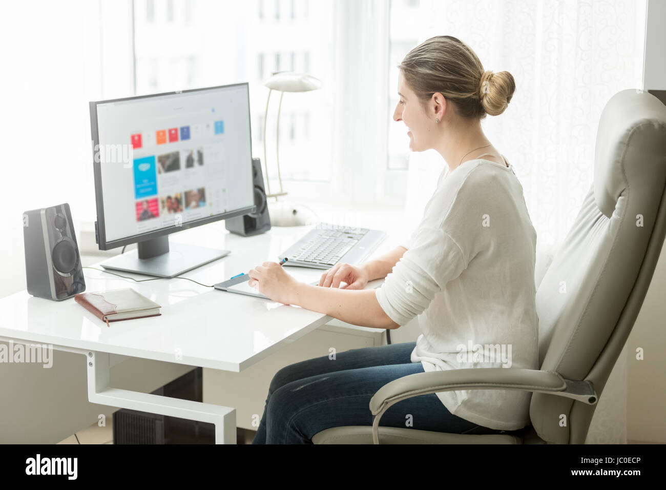 Portrait of young female designer working at home office at computer ...