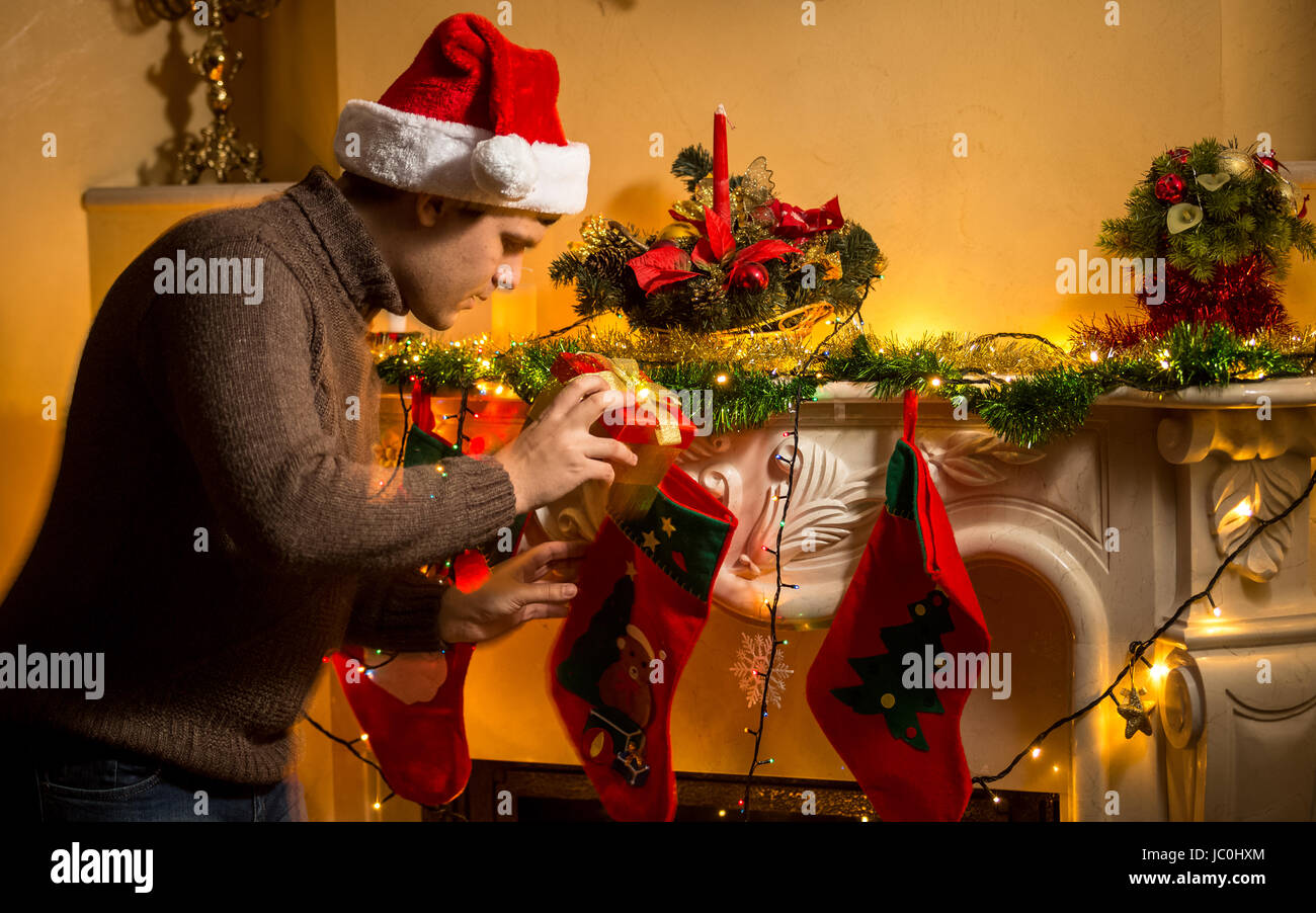 portrait of young father putting gifts in christmas stockings at fireplace