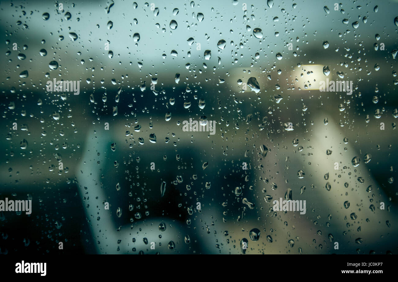 Photo of blurred building through window with raindrops - Stock Image