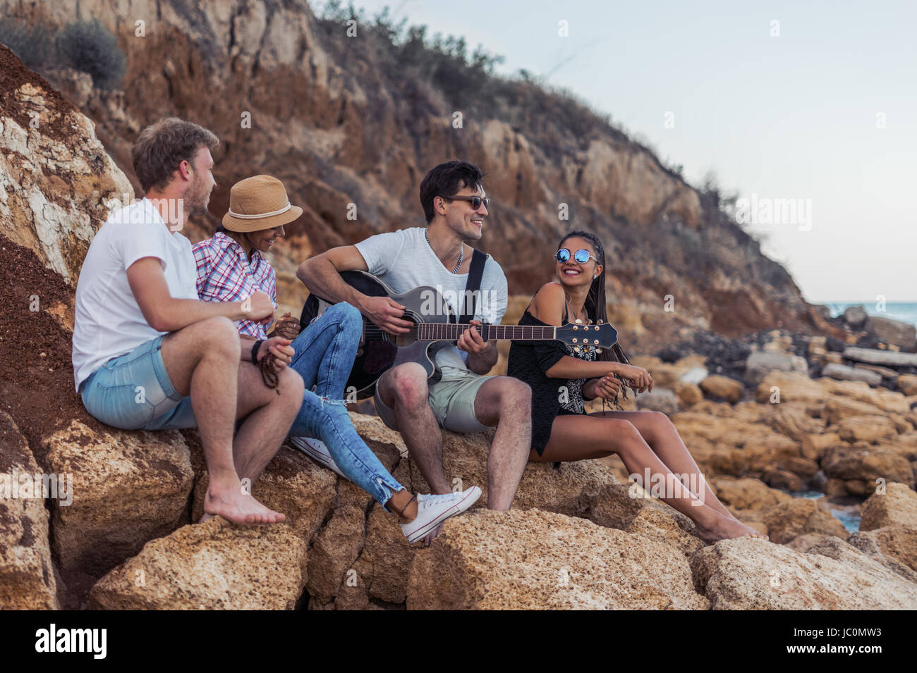 friends sitting on stones on beach. man is playing guitar. - Stock Image
