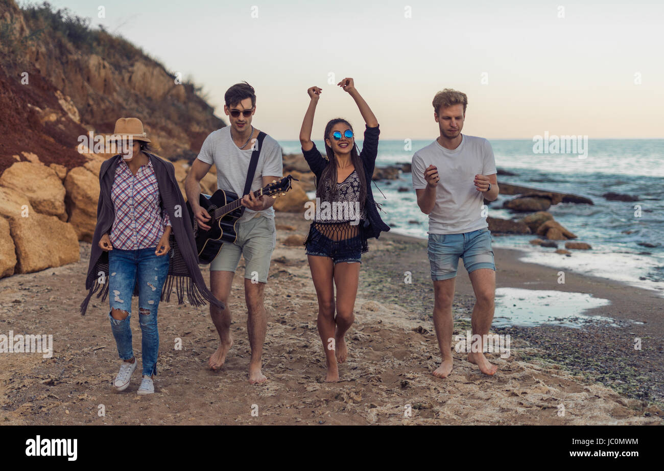 group of young and cheerful friends walking on beach - Stock Image