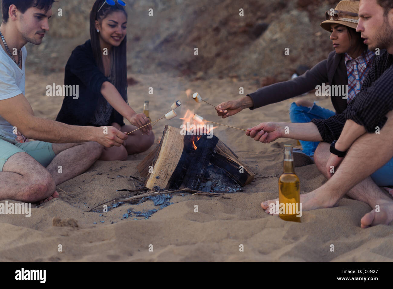 Friends on a wild beach lit a bonfire and fry marshmallows - Stock Image