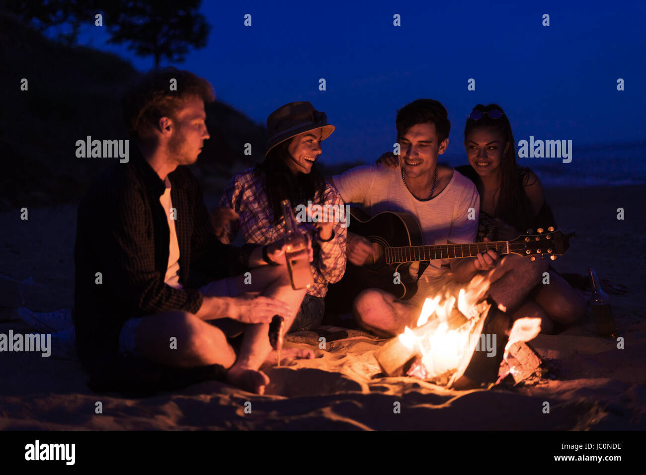 friends sitting on the beach. man is playing guitar. - Stock Image