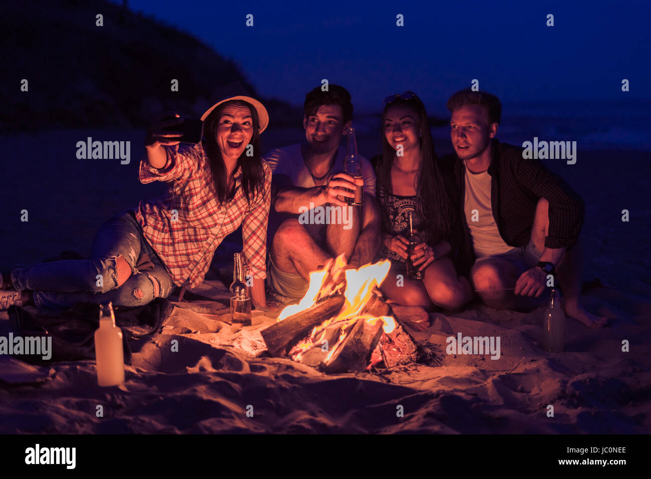 riends sitting on beach and take selfie - Stock Image