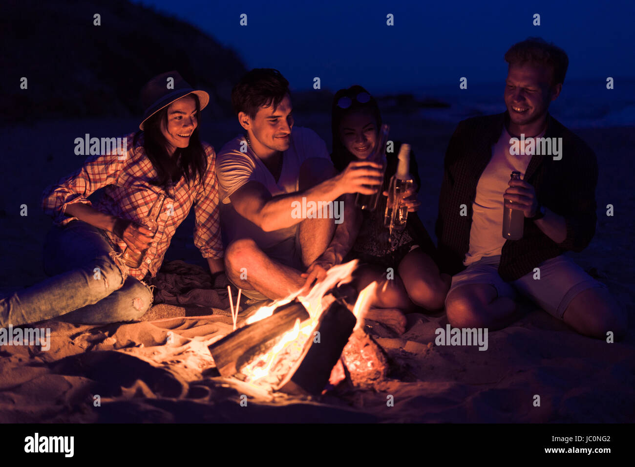 friends sitting on the beach clink glasses near bonfire - Stock Image