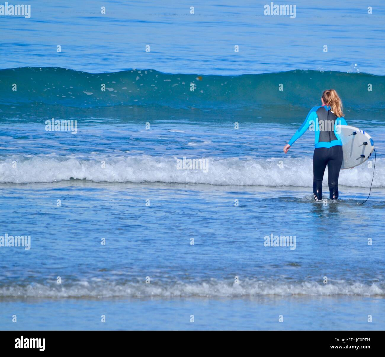 Girl walking into ocean with surfboard - Stock Image