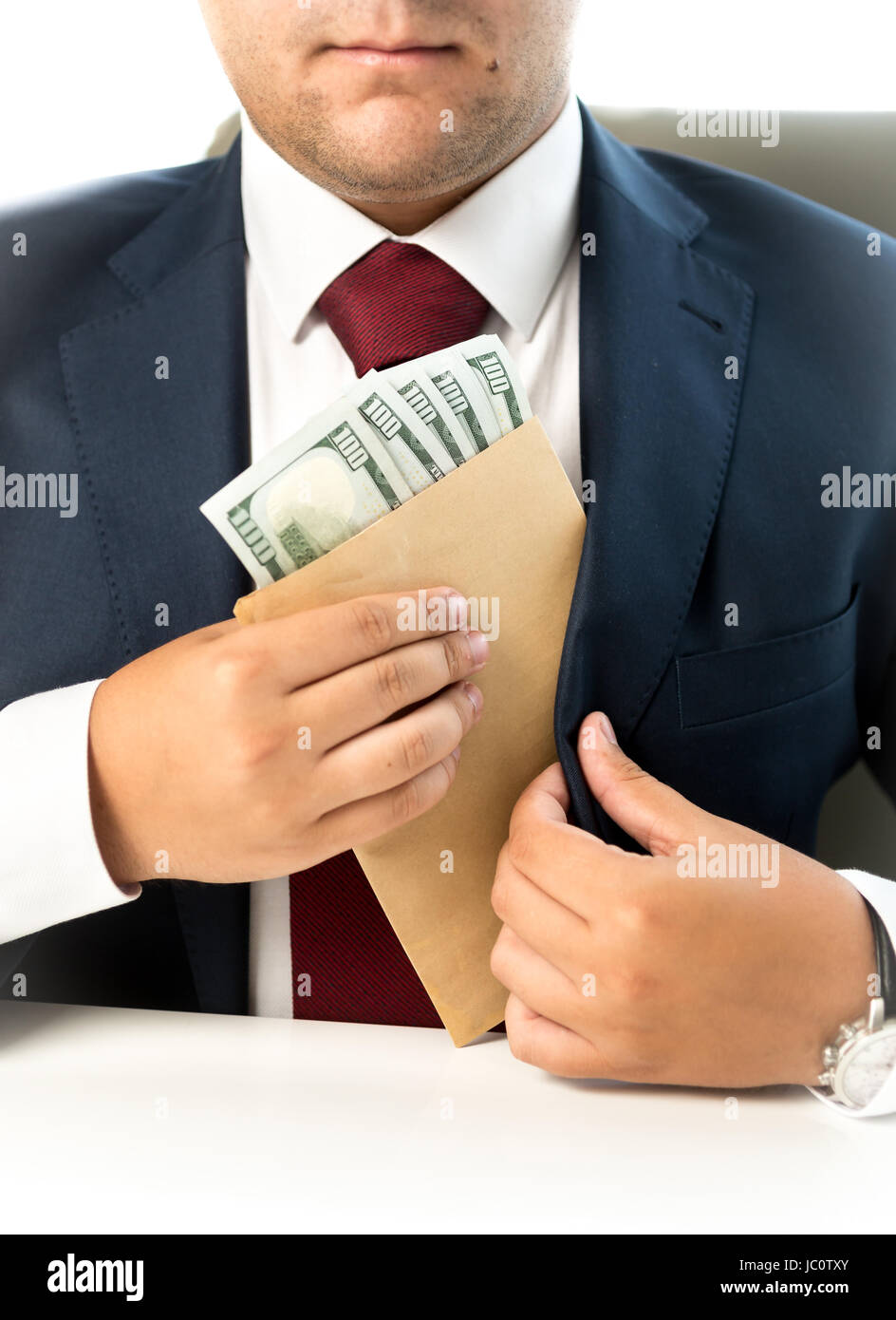 Closeup photo of businessman hiding envelope with money in pocket at jacket - Stock Image