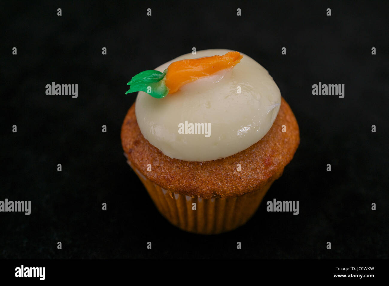 Carrot cupcake garnished with decorated with whipped cream frosting and a carrot, on black background - Stock Image