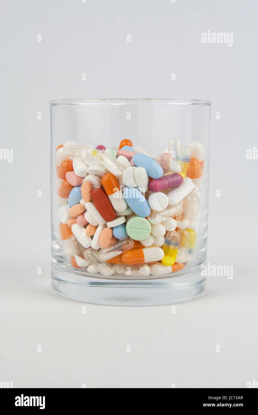 glass full of pills Stock Photo