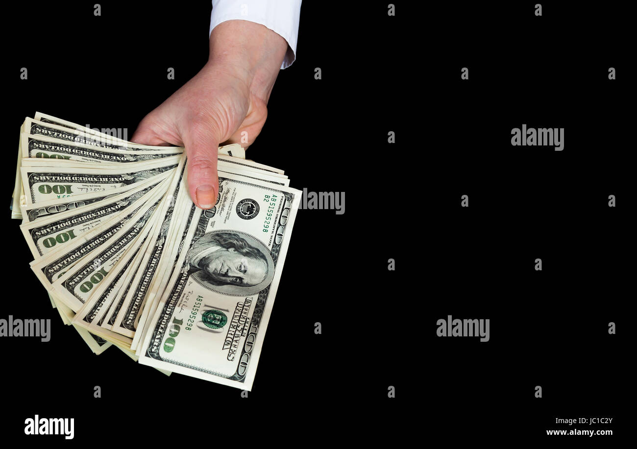 Money in a female hand close up on a black background - Stock Image