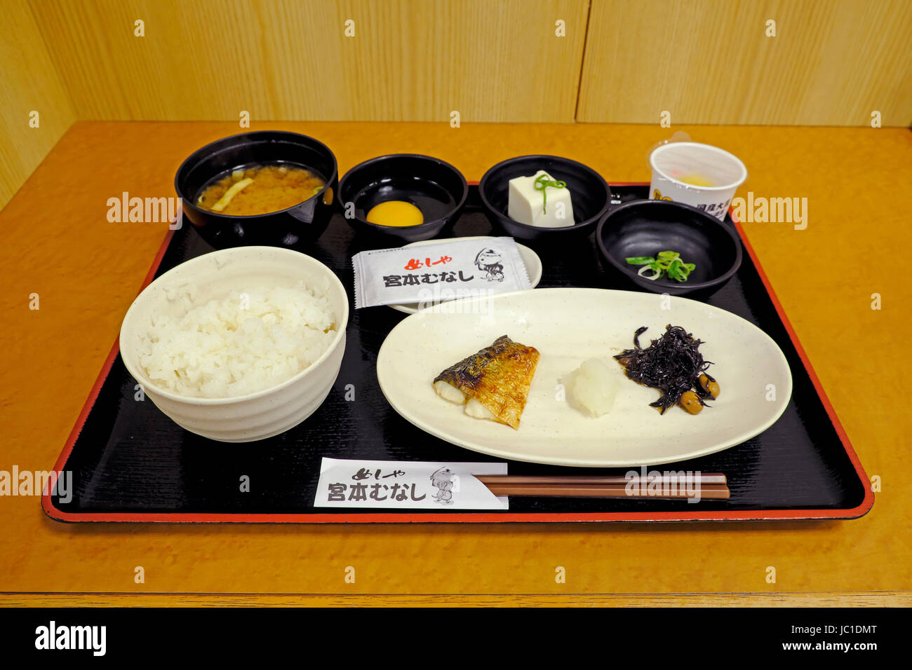 A plate of simple Japanese breakfast in Osaka; rice with fish, raw egg, natto (sticky fermented soybeans), pickles - Stock Image