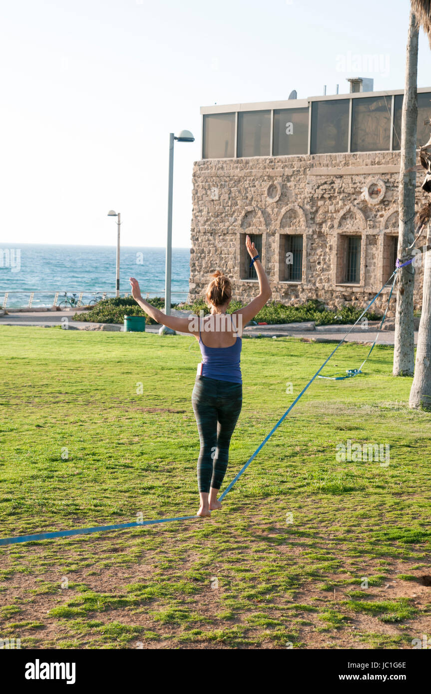 woman Slacklining in Charles Clore park, Tel Aviv-Jaffa with Elinor Cohen. Photography: Ilan Rosen - Stock Image