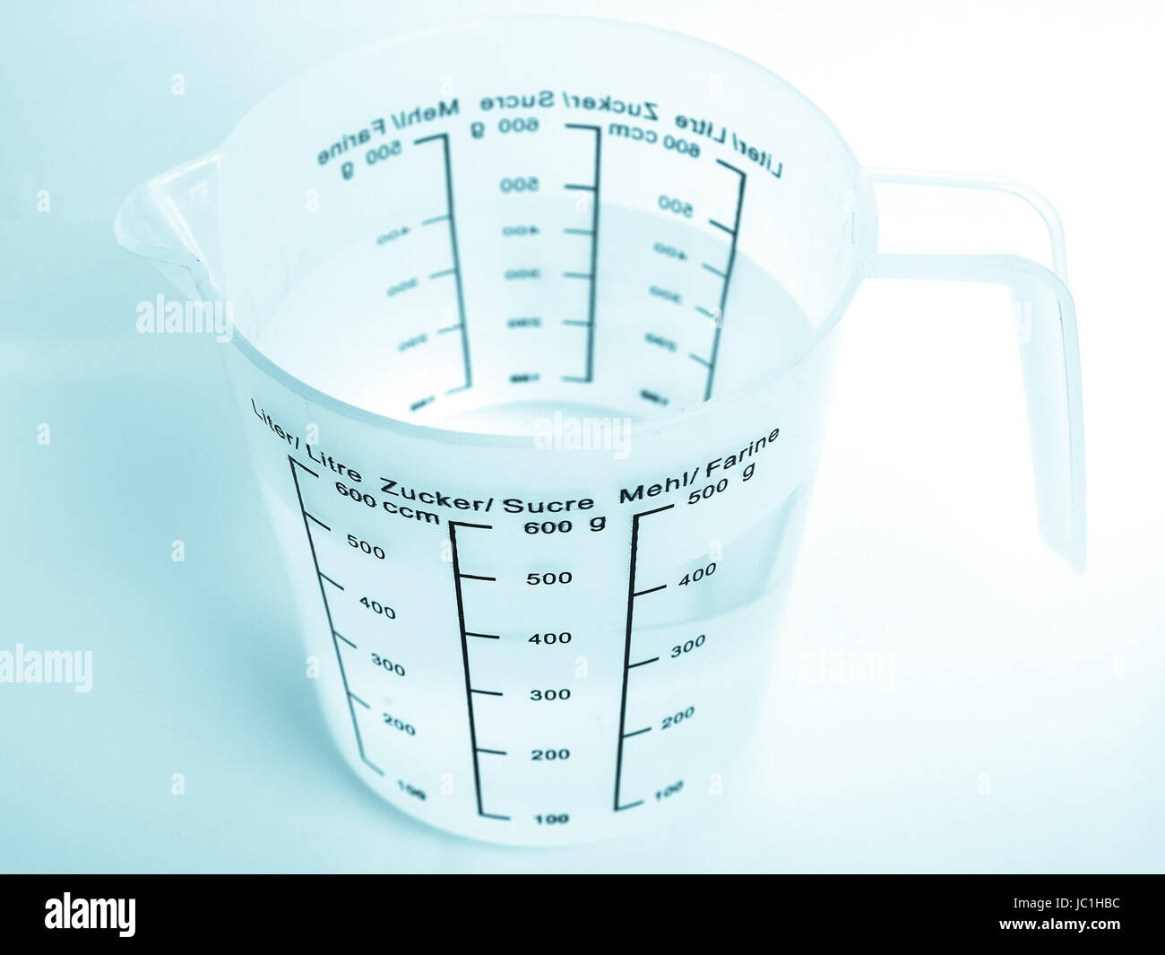 Measuring cup with metric scales for water, sugar and flour - cool cyanotype Stock Photo