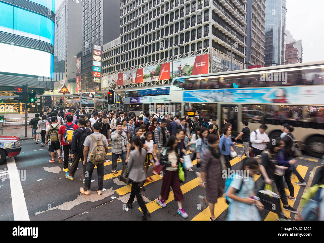 HONG KONG - APRIL 26, 2017: People, captured with blurred motion, cross Nathan road in the very crowded Mong Kok - Stock Image