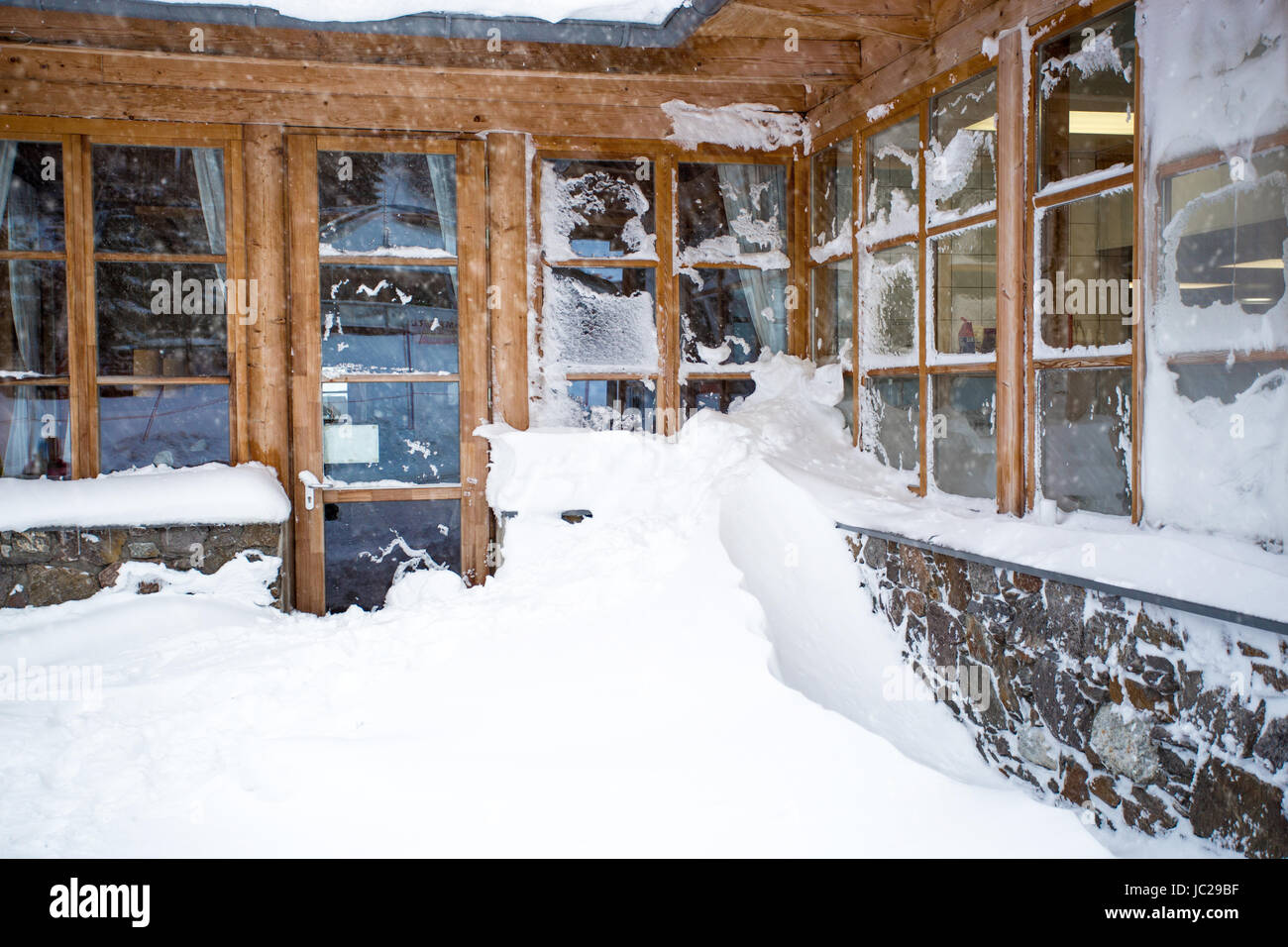 e18fa2048dc2 Classic Austrian wooden house with big windows covered by snow at snowstorm