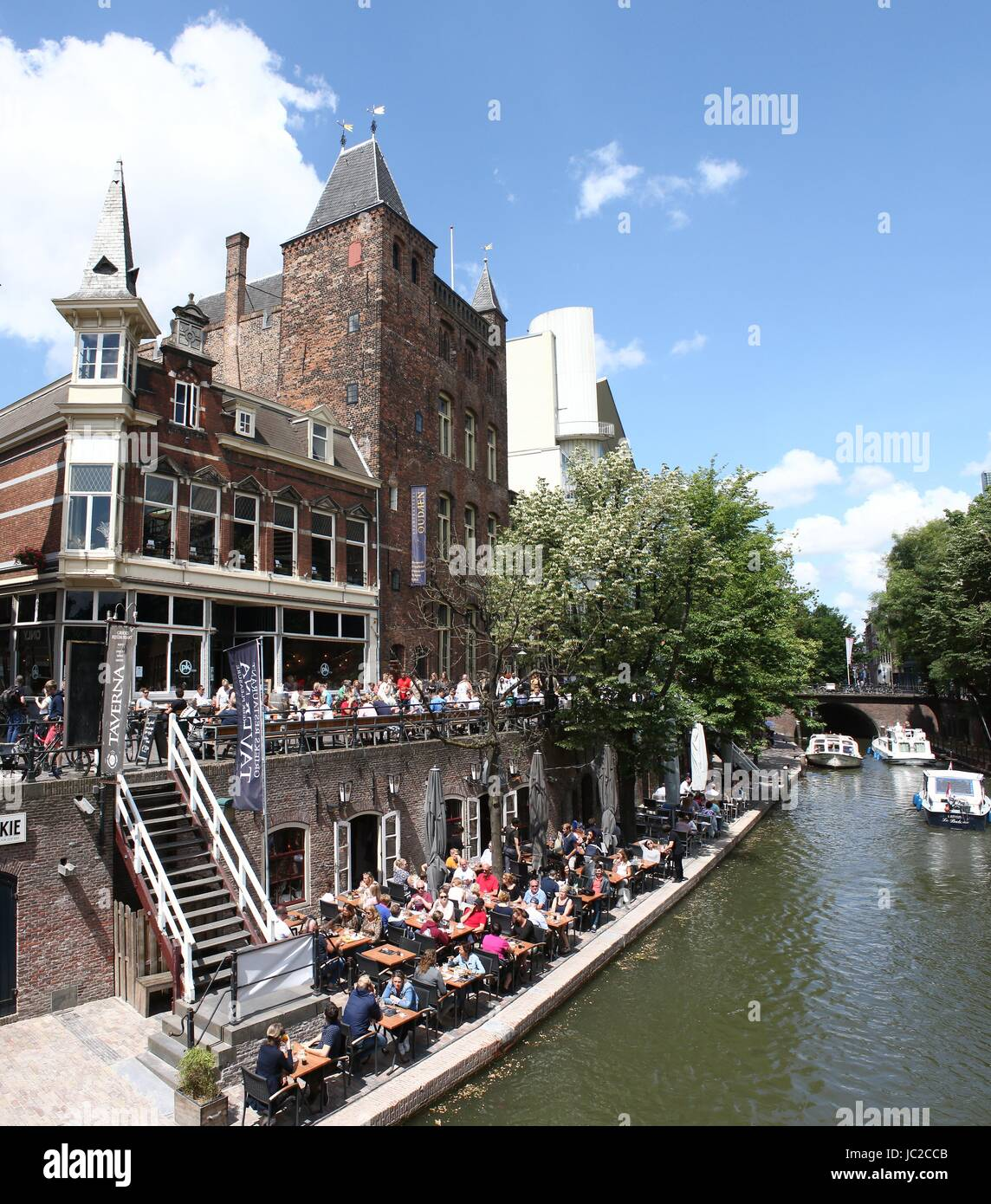 Tourists on a summer terrace along Oudegracht canal in inner city of Utrecht, Netherlands with Medieval 'Stadskasteel - Stock Image