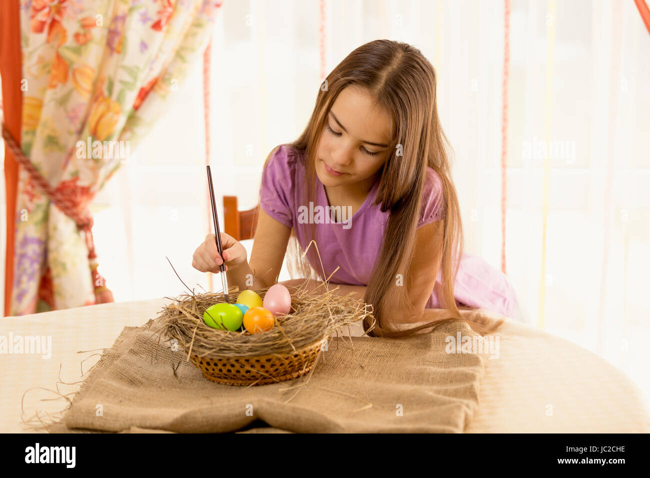 Portrait of cute girl decorating easter eggs in basket Stock Photo
