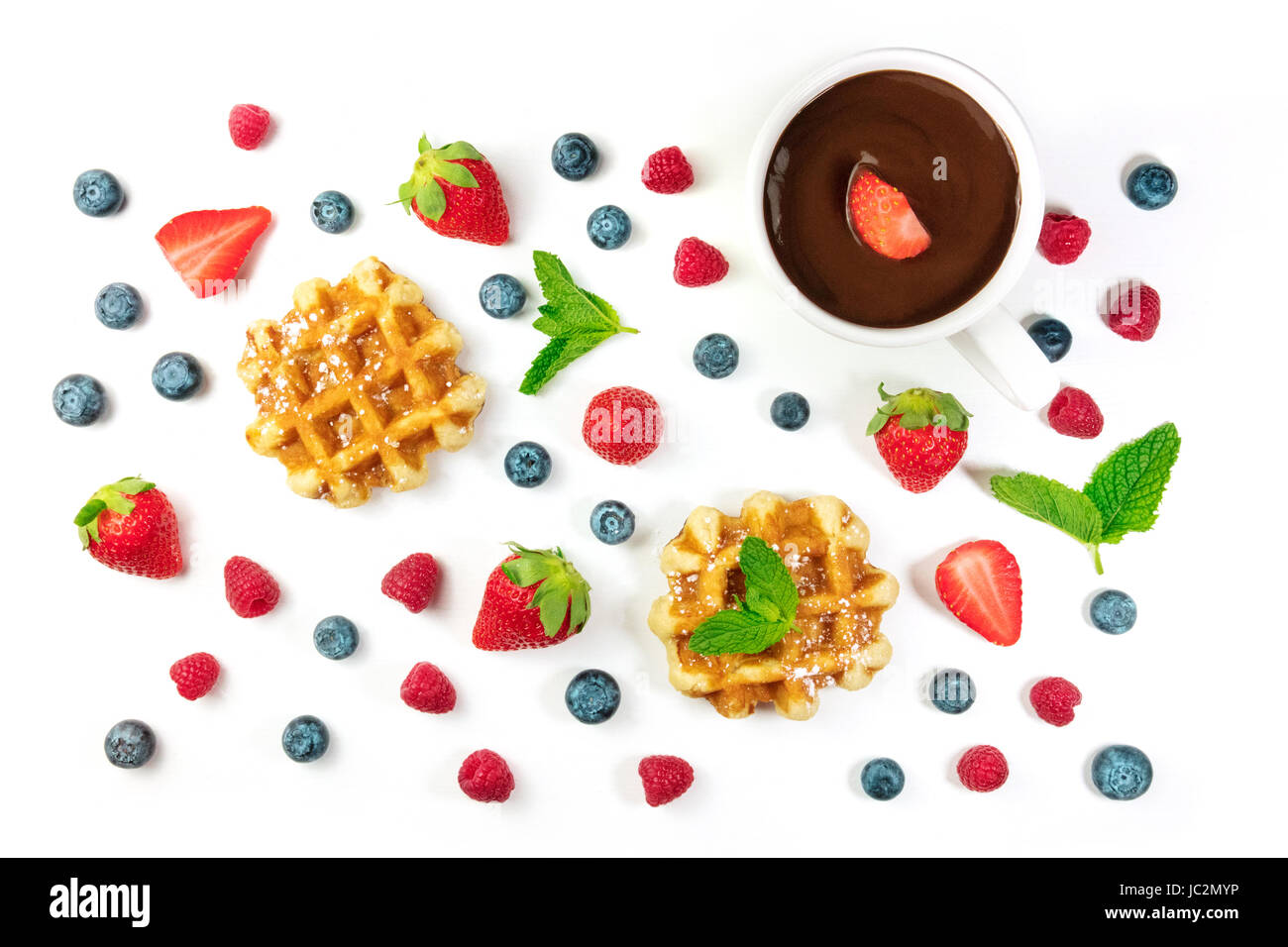 Belgian waffles with fresh fruit, mint leaves, and chocolate - Stock Image