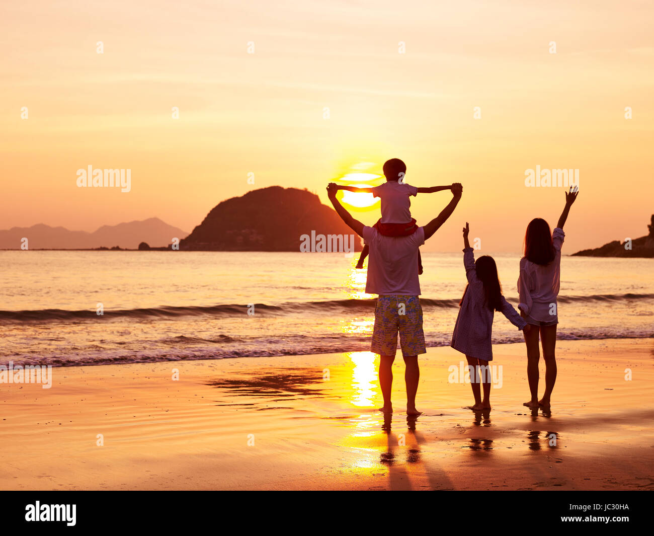 asian family standing on beach watching and enjoying the sunrise or sunset. - Stock Image