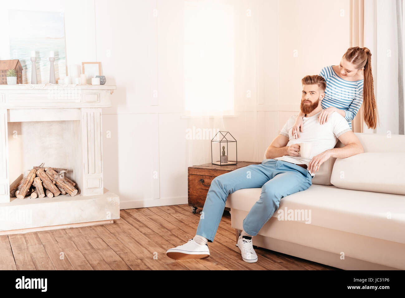 Beautiful young woman hugging handsome bearded man sitting on sofa at home - Stock Image