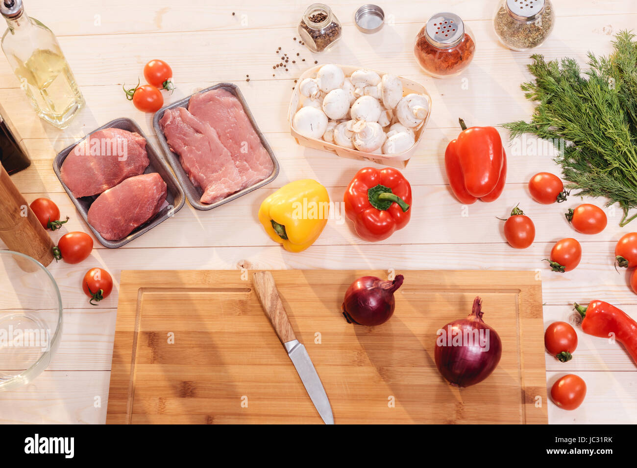 Close-up view of fresh vegetables and raw meat on wooden table - Stock Image