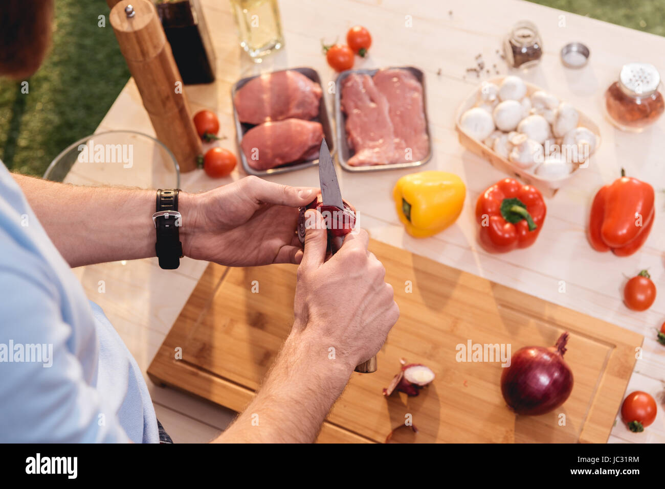 Cropped shot of man cutting fresh onion at wooden cutting board for barbecue - Stock Image