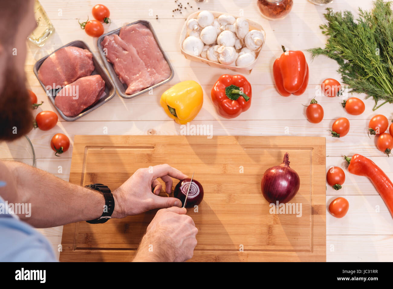 Top view of man cutting fresh onion at wooden cutting board for barbecue - Stock Image