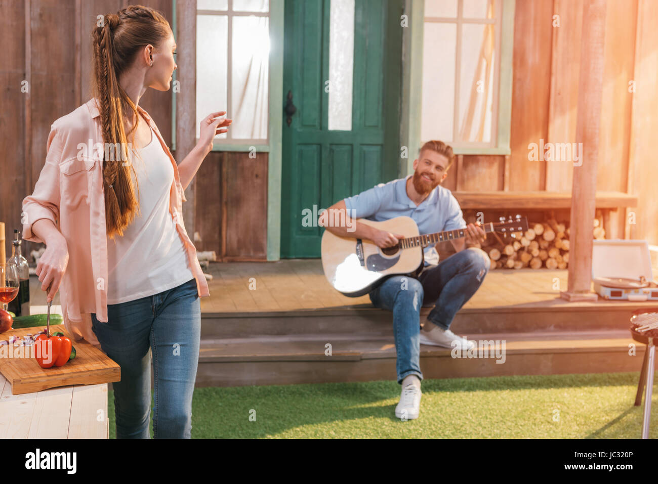 man and woman resting on porch, man playing on guitar - Stock Image
